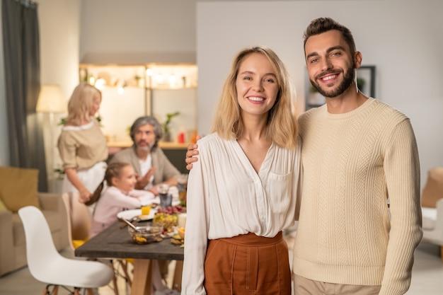 Gelukkig jong aanhankelijk stel in vrijetijdskleding dat naar je kijkt met een brede glimlach op de achtergrond van hun ouders en kinderen aan een feestelijke tafel