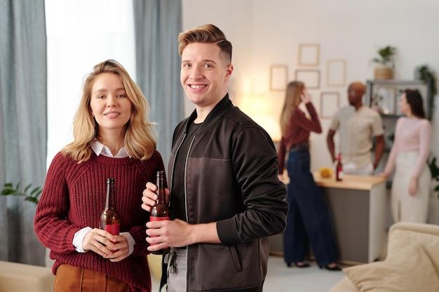 Gelukkig jong aanhankelijk stel met flessen bier die naar je kijken met een brede glimlach terwijl je geniet van een thuisfeestje tegen kletsende vrienden