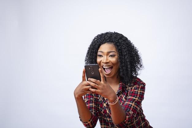 Gelukkig jong afrikaans vrouwtje met behulp van haar telefoon en opgewonden over iets