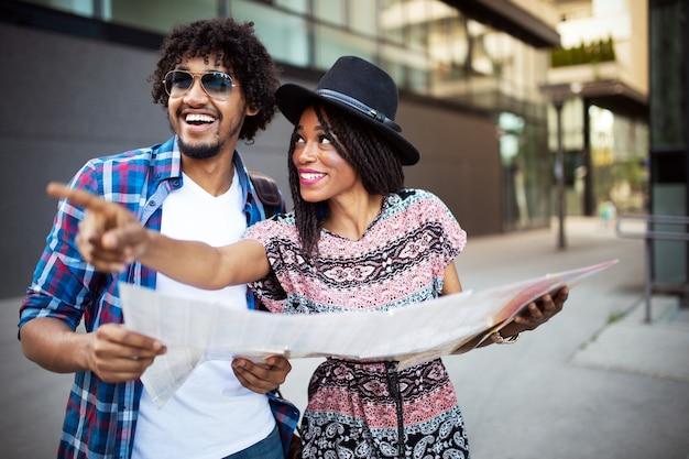 Gelukkig jong afro-amerikaans stel reizigers die kaart in handen houden
