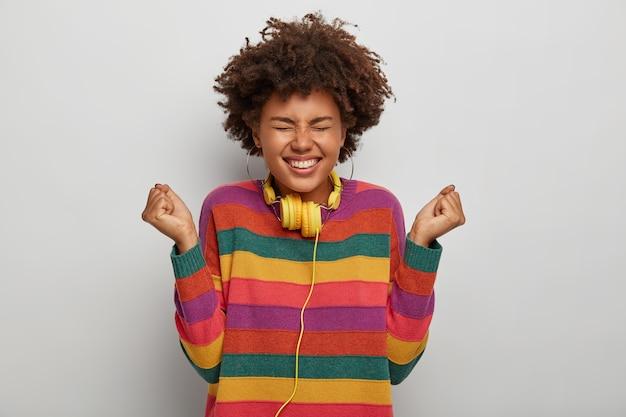 Gelukkig jong afro meisje balde vuisten, proost aangenaam moment, lacht aangenaam, breed lacht, koptelefoon om nek draagt