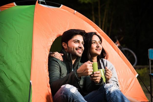 Gelukkig jong aziatisch indisch stel kamperen, zittend bij tent op camping ontspannen en thee drinken.