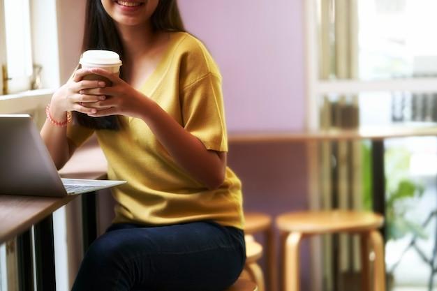 Gelukkig jong aziatisch meisje dat hete koffiedocument kop houdt Premium Foto