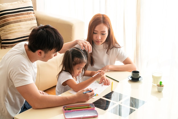 Gelukkig jong aziatisch meisje met haar lieve ouders huiswerkopdracht een opleiding en samen quality time doorgebracht. aziatische familie, sociale afstand, homeschooling, thuiswerken of liefdesconcept
