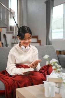 Gelukkig jong aziatisch meisje zittend op de bank in de woonkamer en het gebruik van mobiele telefoon.