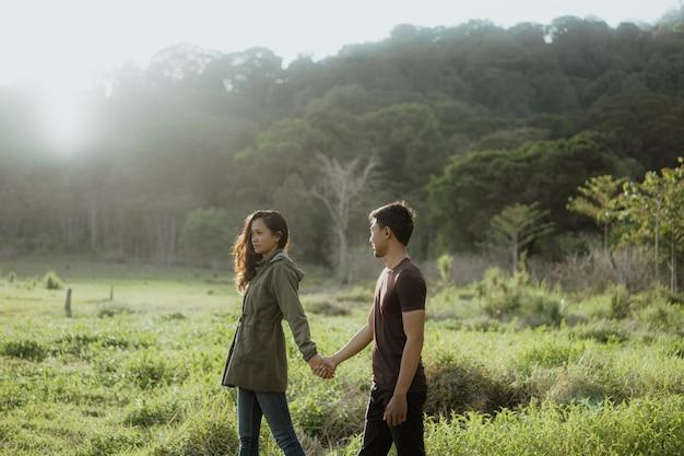 Gelukkig jong aziatisch paar dat in platteland van aard geniet