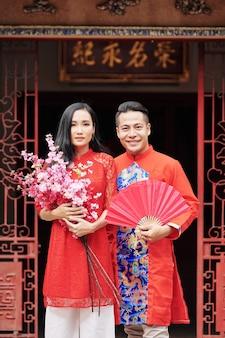 Gelukkig jong aziatisch stel dat buiten staat met een ventilator van rood papier en bloeiende perziktakken na het vieren van het lentefestival