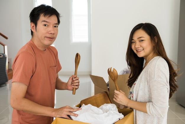 Gelukkig jong aziatisch stel pakt keukengereedschap uit op een kartonnen doos nadat ze alle spullen naar een nieuw huis hebben verplaatst.