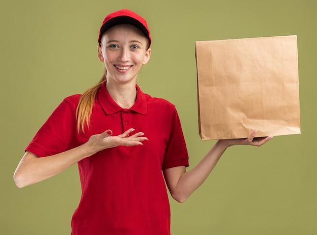 Gelukkig jong bezorgmeisje in rood uniform en pet met pakket presenterend met arm glimlachend zelfverzekerd