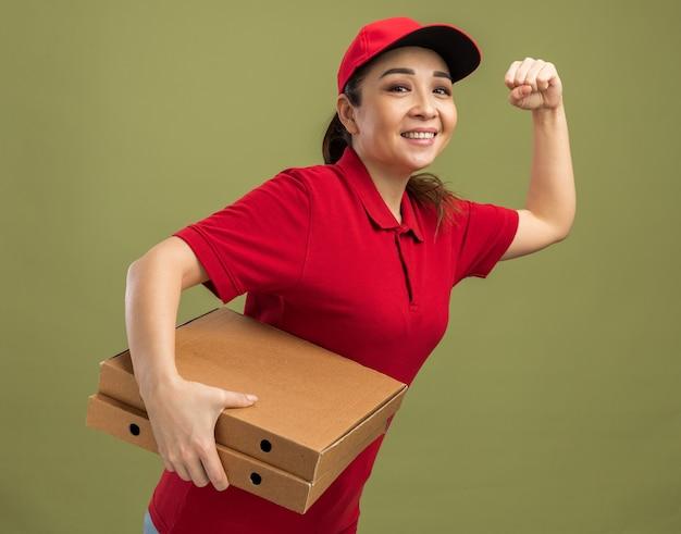 Gelukkig jong bezorgmeisje in rood uniform en pet rush running voor het leveren van pizzadozen voor klant over groene achtergrond