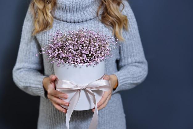 Gelukkig jong blond meisje in een lichtgrijze trui houdt een boeket bloemen in haar handen op een donkergrijze monochrome achtergrond.