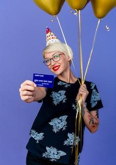 Gelukkig jong blond partijmeisje die glazen en verjaardag glb houden die ballons houden en uit creditcard kijken die camera bekijken die op purpere achtergrond wordt geïsoleerd