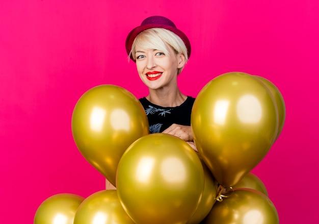 Gelukkig jong blond partijmeisje die partijhoed dragen die zich achter ballons bevinden die camera bekijken die op karmozijnrode achtergrond wordt geïsoleerd