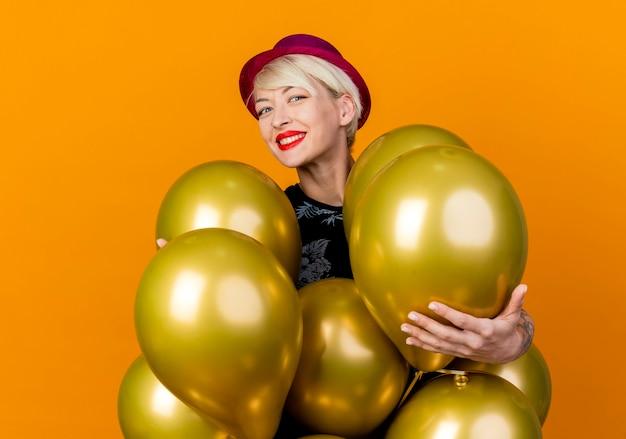 Gelukkig jong blond partijmeisje die partijhoed dragen die zich achter ballons bevinden die hen aanraken camera kijken en glimlachen geïsoleerd op oranje achtergrond
