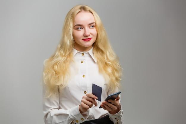 Gelukkig jong blondemeisje die plastic creditcard tonen terwijl het houden van mobiele telefoon