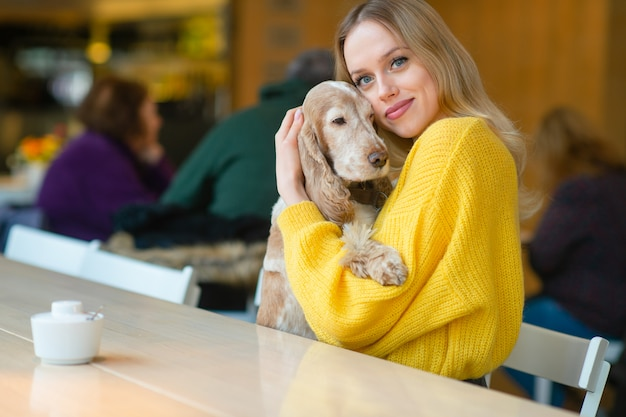 Gelukkig jong blondemeisje in gele sweaterzitting bij de lijst in caffe en het koesteren van haar aanbiddelijke cocker-spaniël