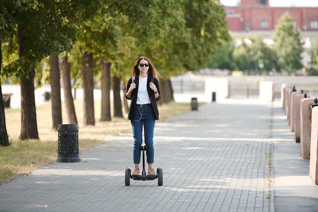 Gelukkig jong casual vrouwtje in zonnebril verplaatsen op elektrische scooter langs de weg tussen rivieroever en rij van groene bomen in de ochtend