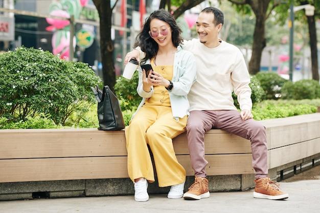 Gelukkig jong chinees stel dat op de bank zit en sociale media op smartphone controleert of foto's plaatst