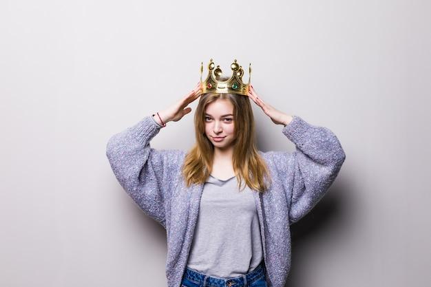 Gelukkig jong die vrouw of tienermeisje in prinseskroon op grijs wordt geïsoleerd