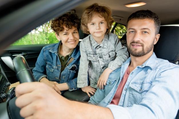 Gelukkig jong eigentijds gezin van drie in denim jassen op zoek naar jou met een glimlach terwijl ze in de auto zitten en naar het platteland gaan
