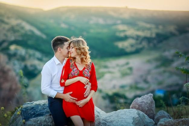 Gelukkig jong familie zwanger mooi meisje met echtgenoot op de klip in bergen over zonsonderganglichten
