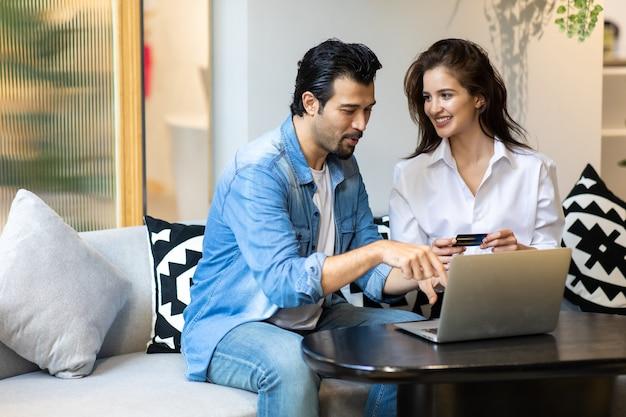 Gelukkig jong familiepaar dat online met laptop computer winkelt. online aankopen doen.