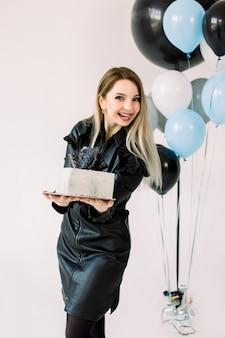 Gelukkig jong feestvarken in zwarte leerkleding, glimlachen, die witte vierkante cake houdt, die zich op de witte achtergrond bevindt. grote luchtballonnen, blauwe, witte en zwarte kleur, op de achtergrond