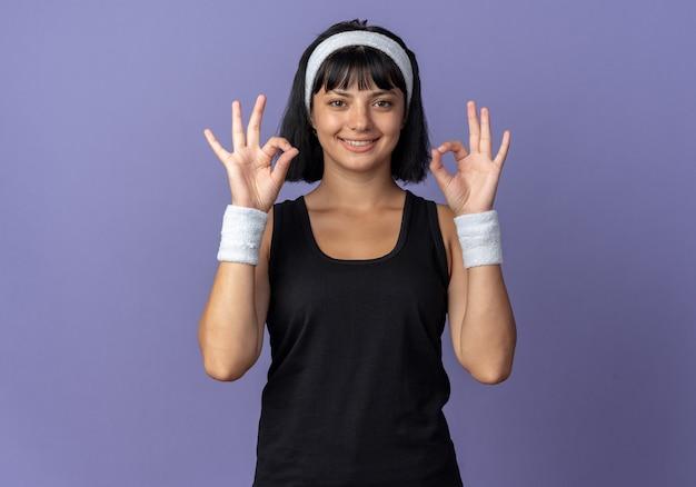 Gelukkig jong fitnessmeisje dat een hoofdband draagt en naar een camera kijkt die vrolijk glimlacht en een goed teken doet dat over een blauwe achtergrond staat