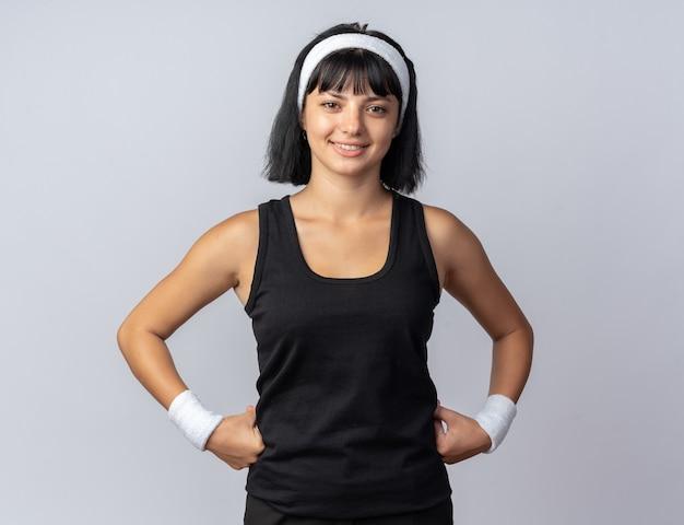 Gelukkig jong fitnessmeisje dat een hoofdband draagt en naar een camera kijkt die zelfverzekerd glimlacht en over wit staat