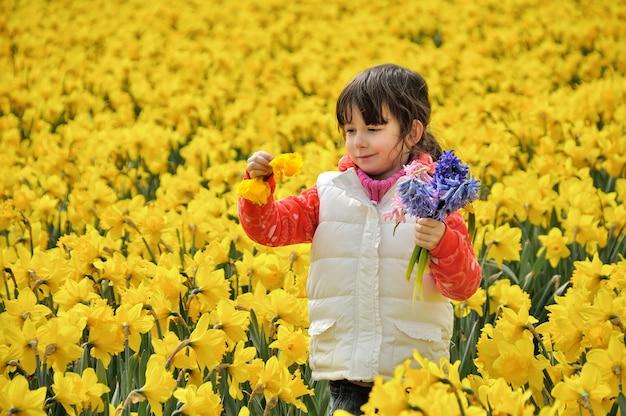 Gelukkig jong geitje met de lentebloemen op geel gele narcissengebied, meisje op vakantiereis in nederland