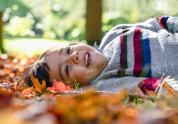 Gelukkig jong geitjejongen die op bladeren bepaalt die onder de boom vallen die met een lachend gezicht naar de hemel kijken