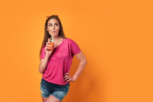Gelukkig jong gen z meisje bedrijf drankje knipoogje kijken camera dragen zonnebril genieten van koele cocktail veel plezier geïsoleerd op gele partij zomer studio achtergrond