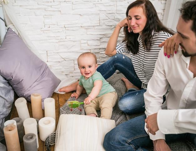 Gelukkig jong getrouwd stel positieve vader en lachende moeder zitten op de vloer met hun charmante zoontje spelen een rammelaar