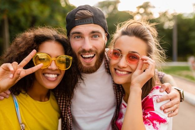 Gelukkig jong gezelschap van emotionele lachende vrienden wandelen in het park met fotocamera, man en vrouw samen plezier