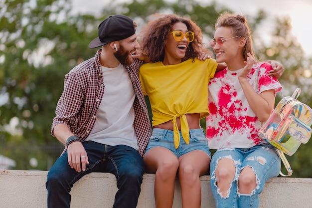 Gelukkig jong gezelschap van glimlachende vrienden die in park zitten, man en vrouwen die samen plezier hebben