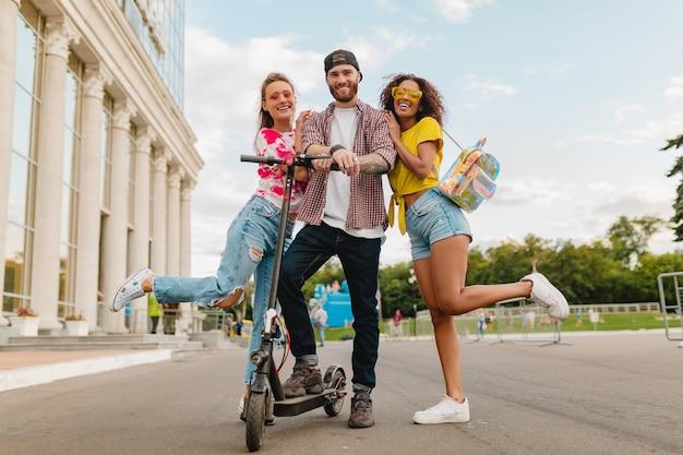 Gelukkig jong gezelschap van glimlachende vrienden die in straat lopen met elektrische step, man en vrouwen die samen pret hebben