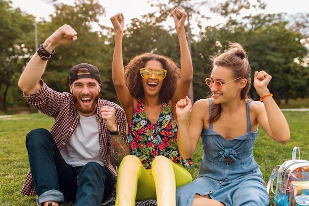 Gelukkig jong gezelschap van glimlachende vrienden die park op gras zitten, man en vrouwen die samen pret hebben