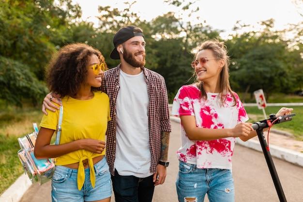 Gelukkig jong gezelschap van lachende vrienden wandelen in het park met elektrische step, man en vrouw samen plezier