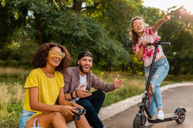 Gelukkig jong gezelschap van lachende vrienden zitten in park op gras met elektrische kick scooter, man en vrouw samen plezier