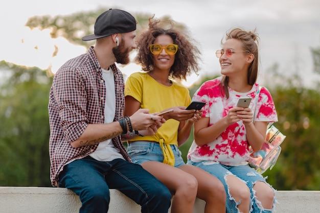 Gelukkig jong gezelschap van lachende vrienden zitten park met behulp van smartphones, man en vrouw met plezier