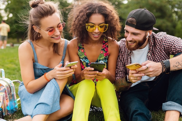 Gelukkig jong gezelschap van lachende vrienden zitten park met behulp van smartphones, man en vrouw samen plezier