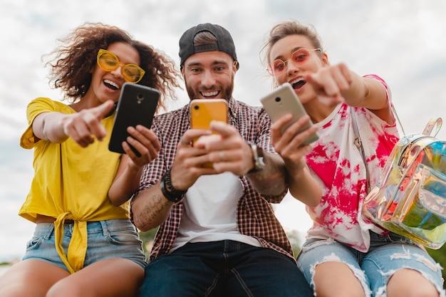 Gelukkig jong gezelschap van lachende vrienden zitten park met behulp van smartphones