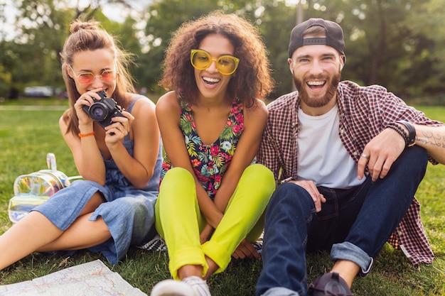 Gelukkig jong gezelschap van pratende lachende vrienden zitten park, man en vrouw samen plezier hebben, reizen met camera