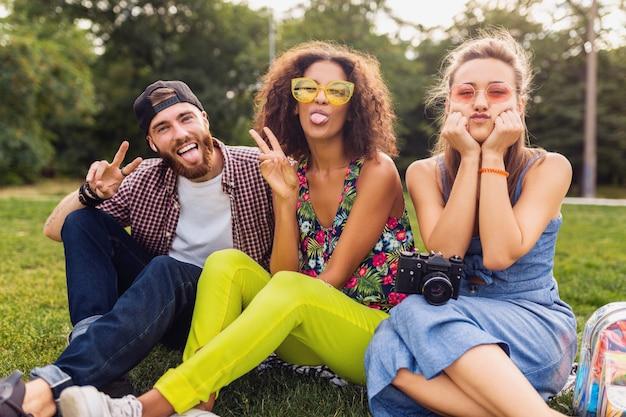 Gelukkig jong gezelschap van vrienden zitten park reizen op zoek in kaart bezienswaardigheden, man en vrouw samen plezier