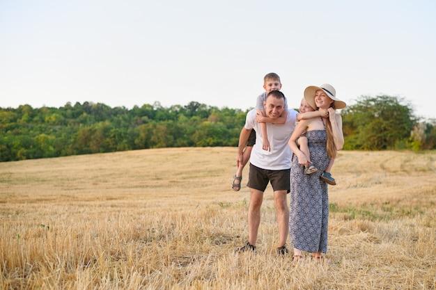 Gelukkig jong gezin. een vader, een zwangere moeder en twee kleine zonen op hun rug. afgeschuind tarweveld