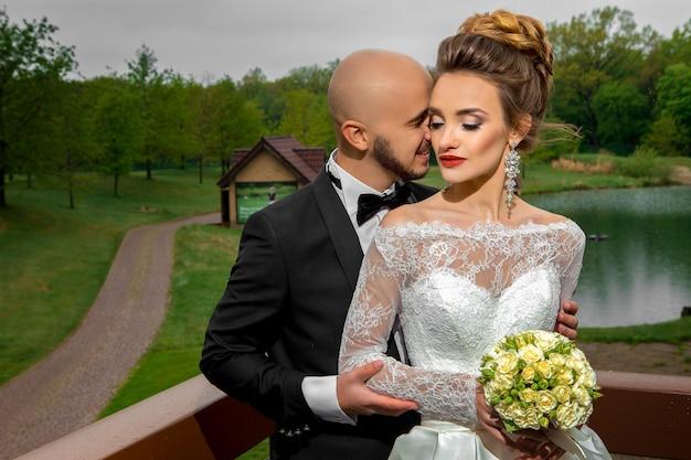 Gelukkig jong gezin in bruiloft pakken buitenshuis knuffelen