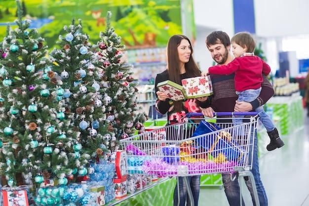 Gelukkig jong gezin in de supermarkt kiest geschenken voor het nieuwe jaar.