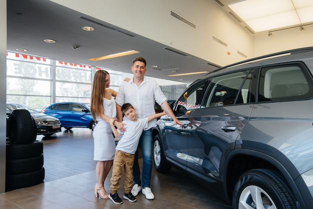 Gelukkig jong gezin kiest en koopt een nieuwe auto bij een autodealer