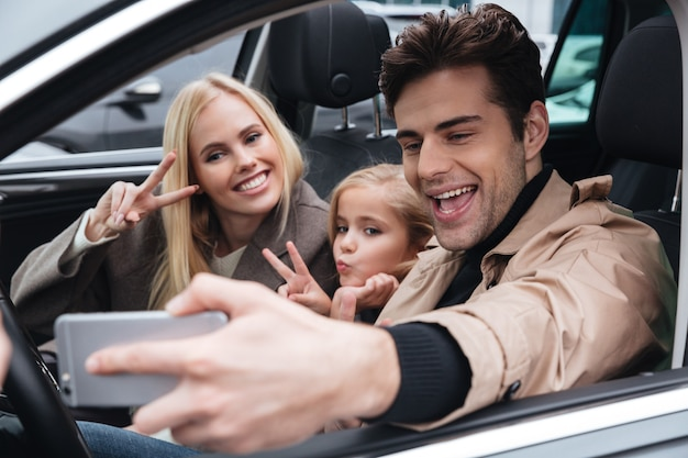Gelukkig jong gezin maken selfie via de mobiele telefoon.