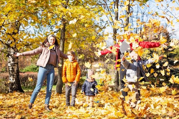 Gelukkig jong gezin met drie kinderen in het herfstpark. liefde en tederheid. wandel in het gouden seizoen.